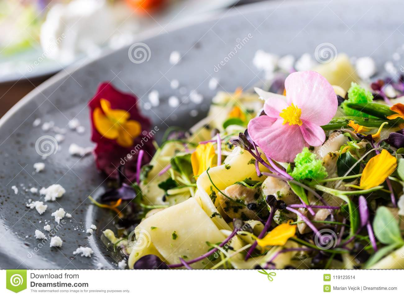 Italian pasta fettucine with chicken pieces and flowers decoration
