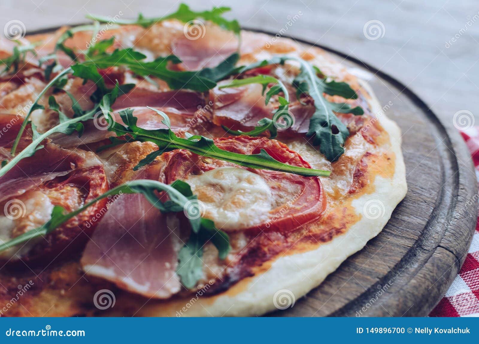 Italian pizza with prosciutto and arugula