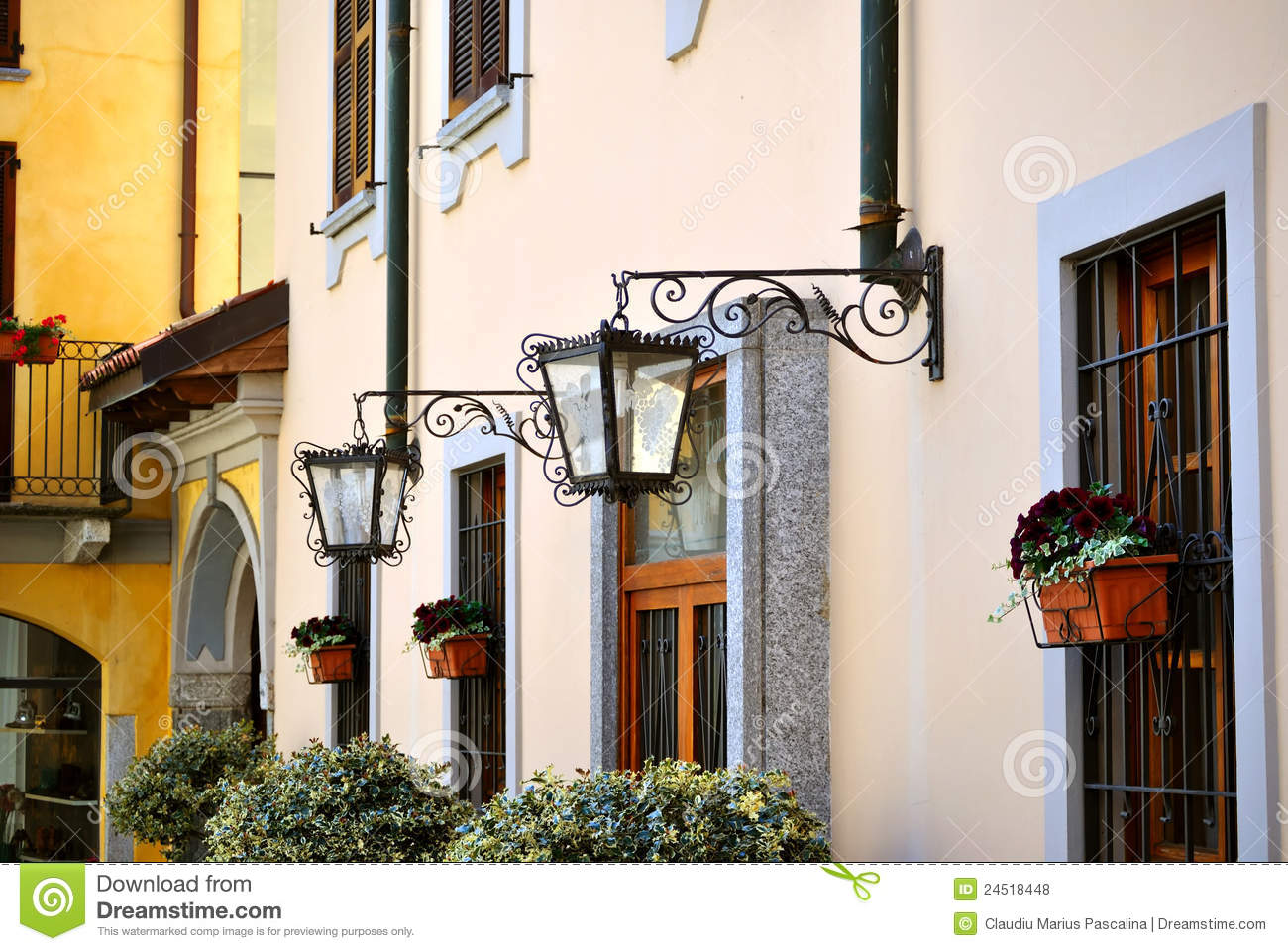 Street lamps on building wall, windows with flowers, architecture ...