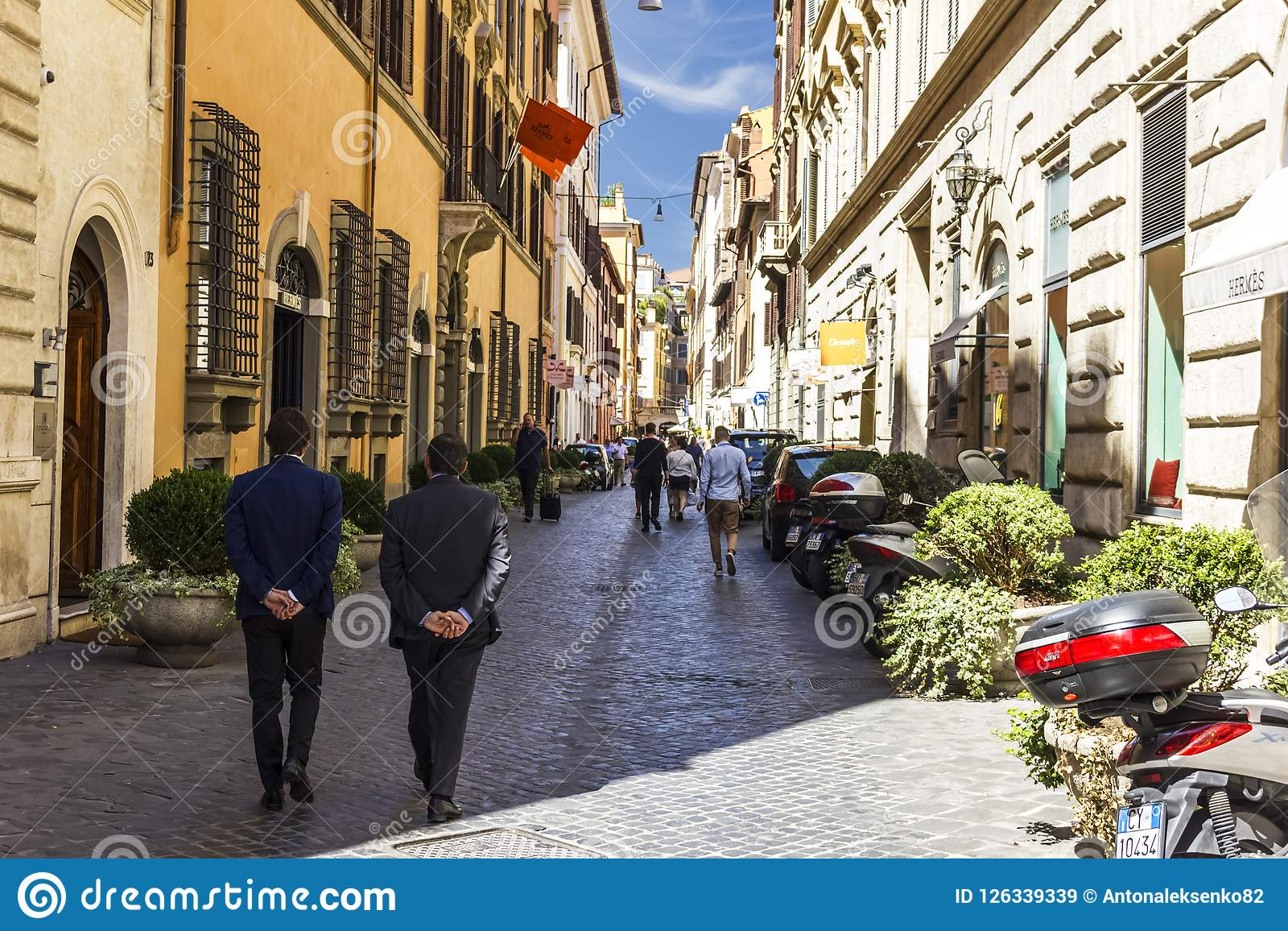 Rome/Italy - August 27, 2018: Busy Roman Street with Fashionable City People, Boutiques and Motor Scooters parking