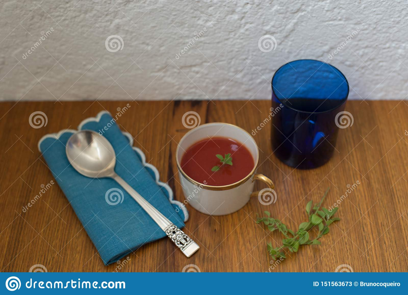 Italian tomato soup oregano leaves served in Chinese porcelain dishes in white and gold colors with silver spoon