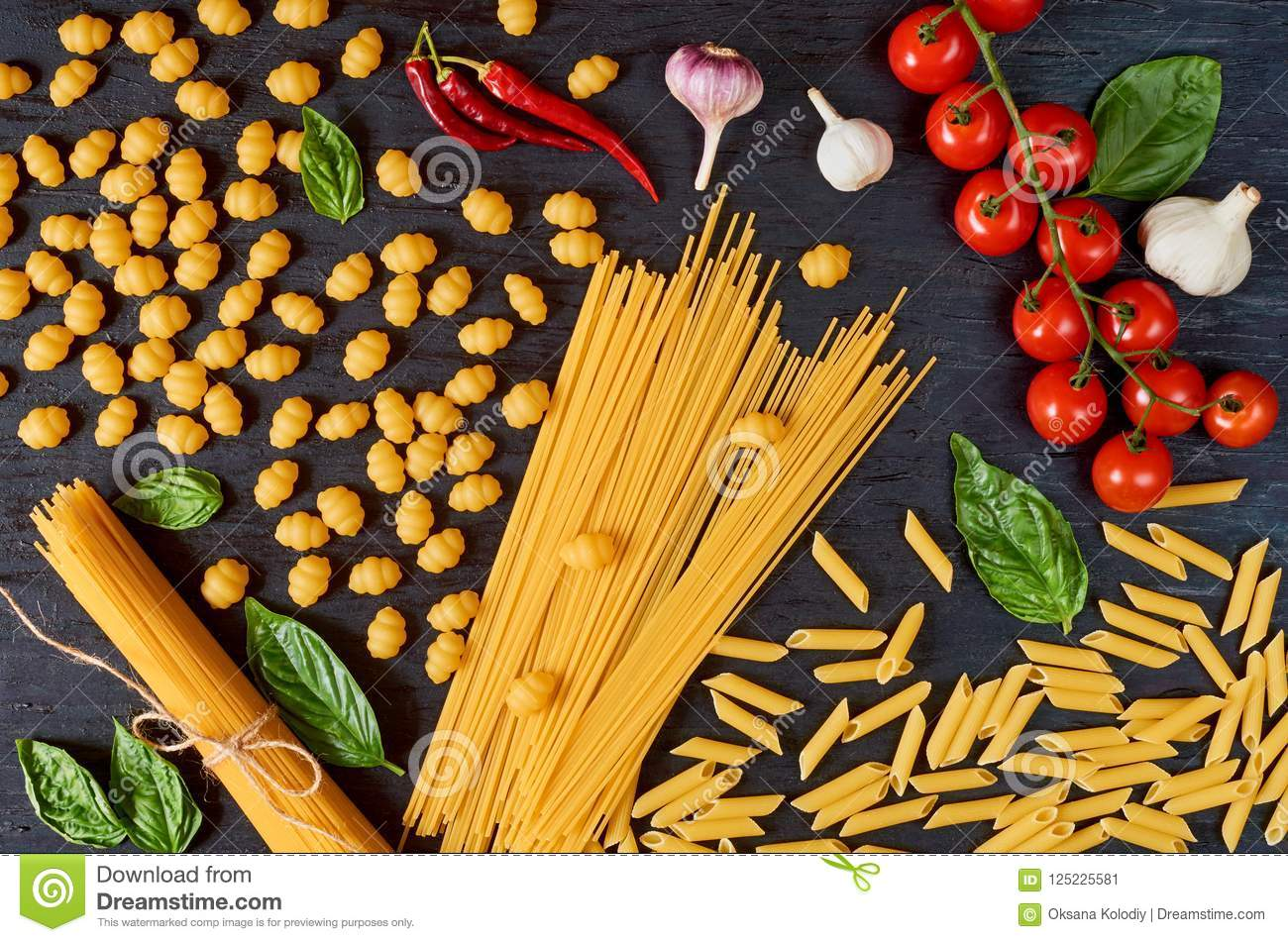 Italian traditional food, spices and ingredients for cooking as basil, cherry tomatoes, chili pepper, garlic and various pasta