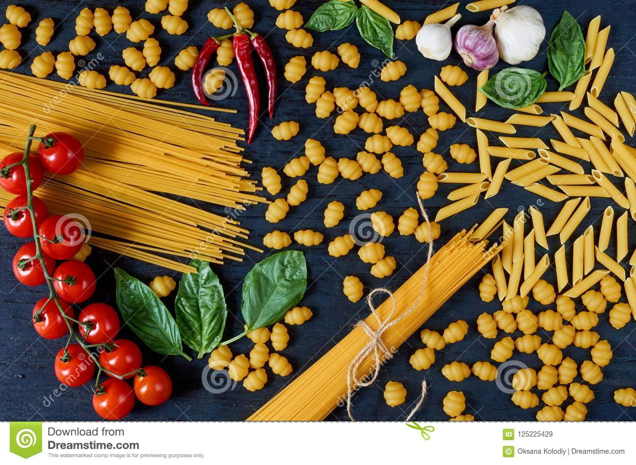 Italian traditional food, spices and ingredients for cooking as basil leaves, cherry tomatoes, chili pepper, garlic, various pasta