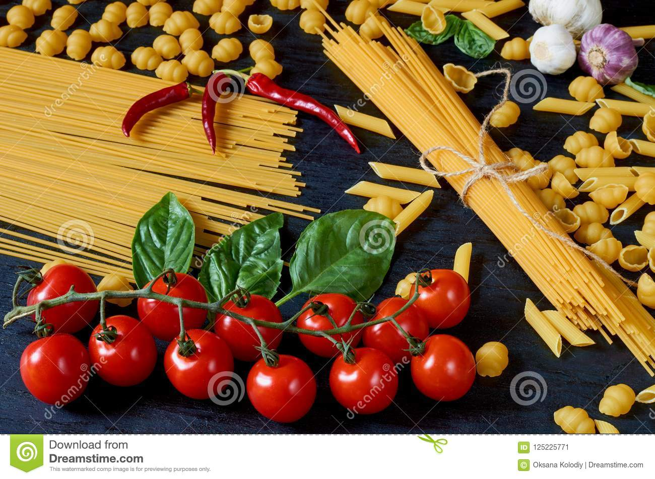 Italian traditional food, spices and ingredients for cooking as cherry tomatoes, chili pepper, garlic, basil leaves and pasta