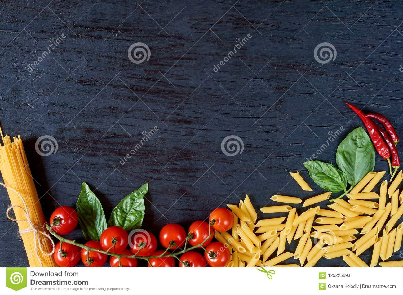 Italian traditional food, spices and ingredients for cooking: basil leaves, cherry tomatoes, chili pepper and various pasta