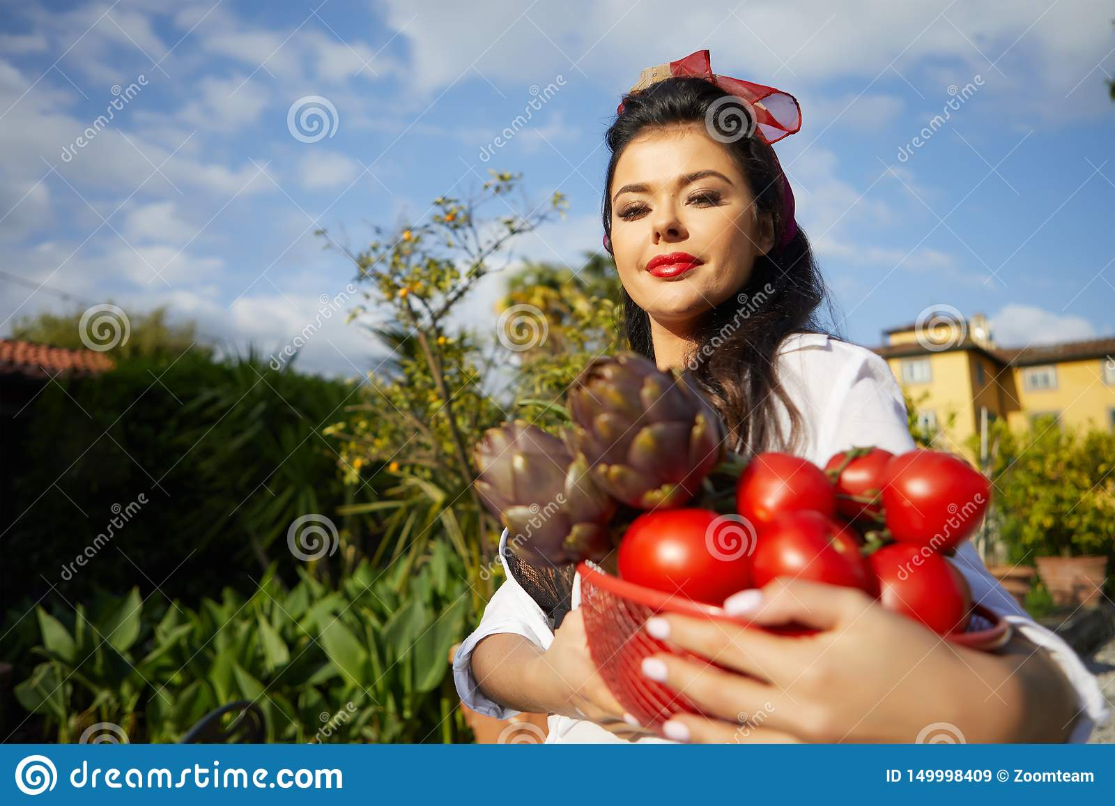 An Italian woman, a housewife, collects vegetables for dinner in a home garden