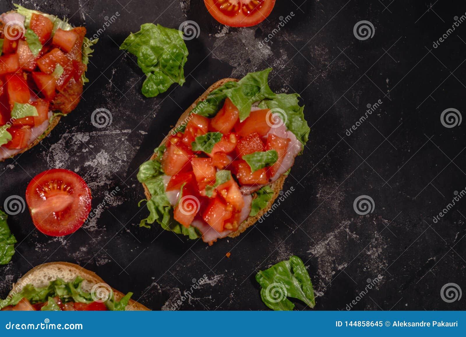 Italiano tradicional Bruschetta com tomates, molho da mussarela, as folhas da salada e o presunto desbastados em um fundo escuro