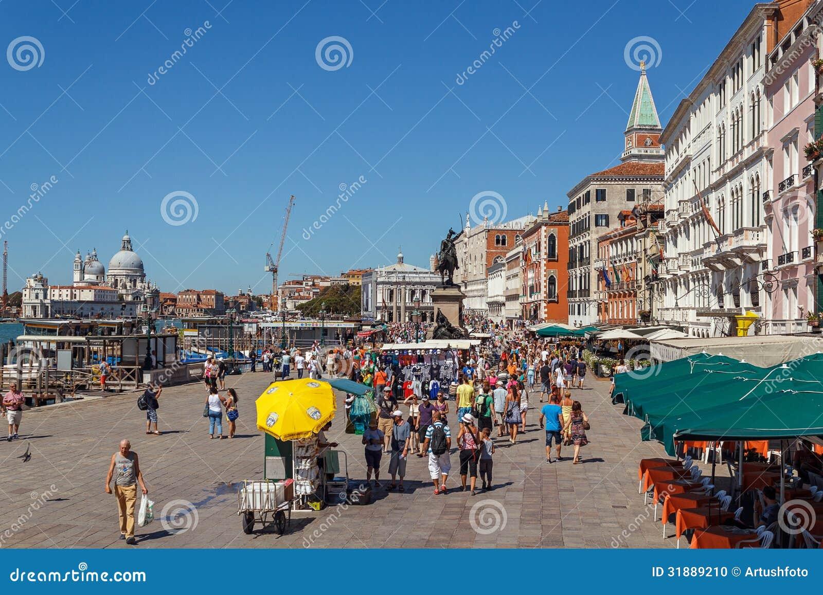 ITALIEN VENEDIG - JULI 2012: Venedig strand med folkmassan av turist- near St Marco Square på Juli 16, 2012 i Venedig. St Marco Sq