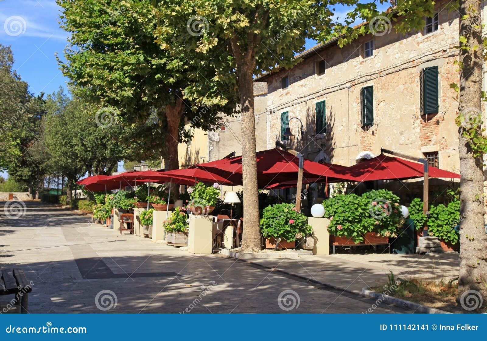 Italienisches Café im Freien mit Regenschirmen und Blumentöpfen im kleinen Schleppseil