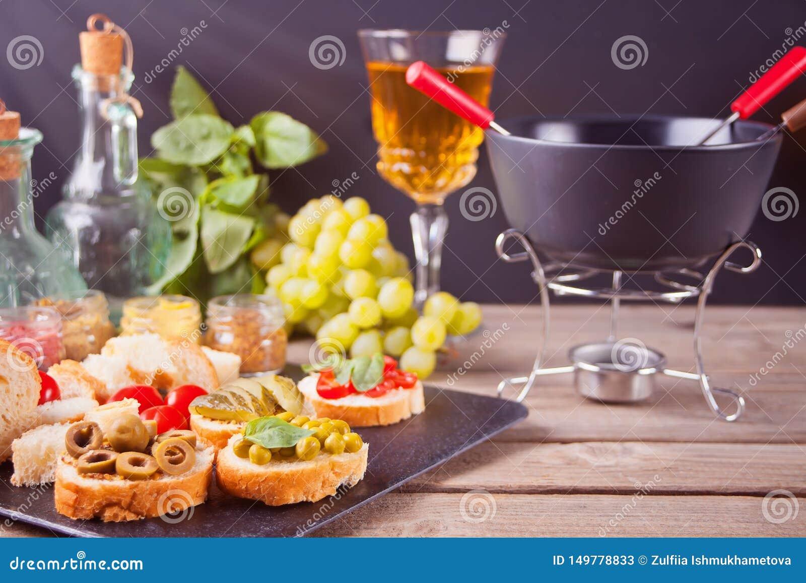 Italiensk bruschetta i sortimentet på plattan, exponeringsglas med vitt vin, druvor, fondue Parti- eller matställebegrepp