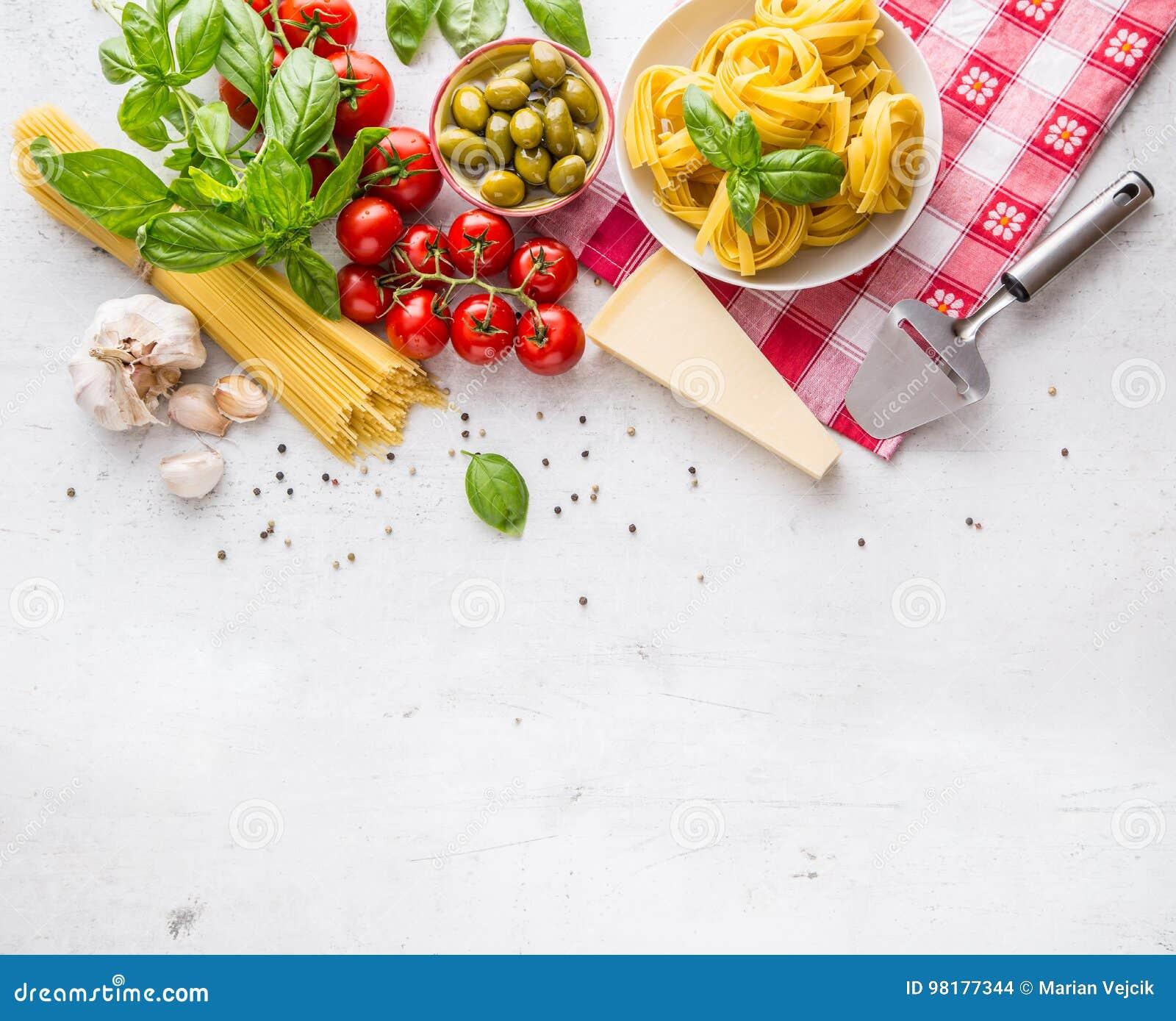 Italiensk matkokkonst och ingredienser på vitbetongtabellen Ost för parmesan för tomater för olivolja för spagettitagliatelleoliv
