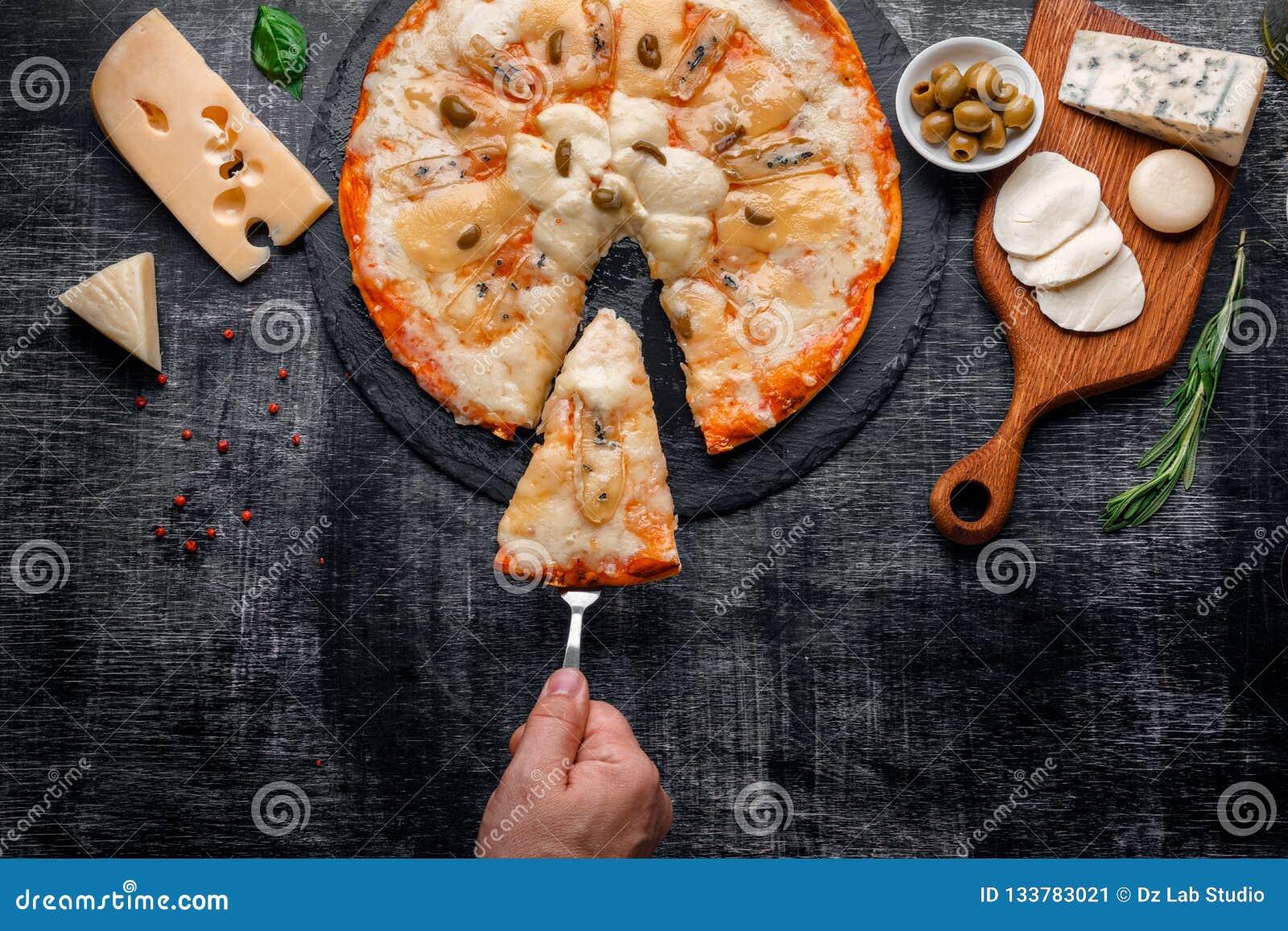 Italiensk pizza med olika slag av ost på en sten och ett svart skrapat kritabräde traditionell matitalienare
