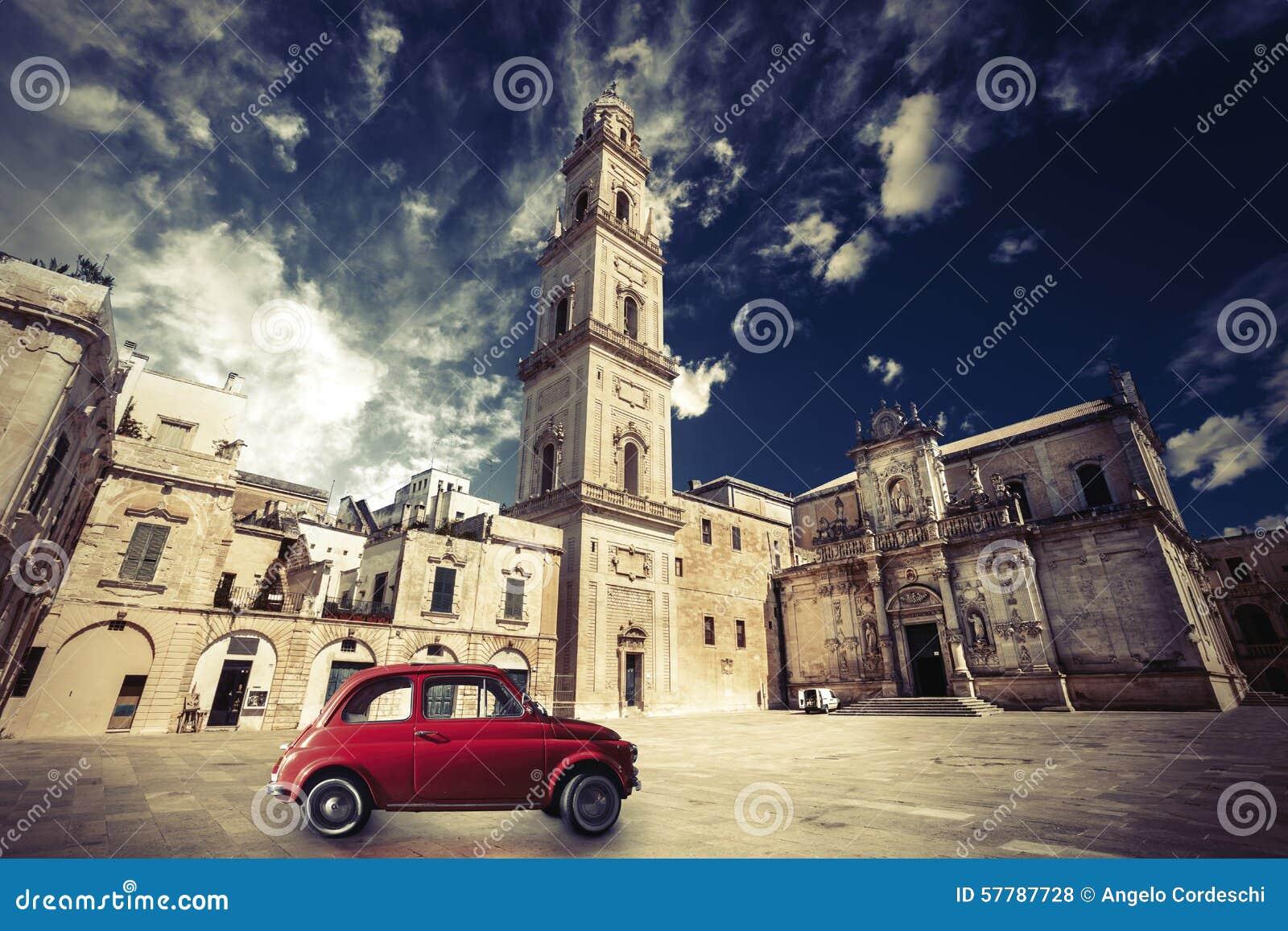 Italiensk plats för tappning, en gammal kyrka med ett klockatorn och gammal liten röd bil