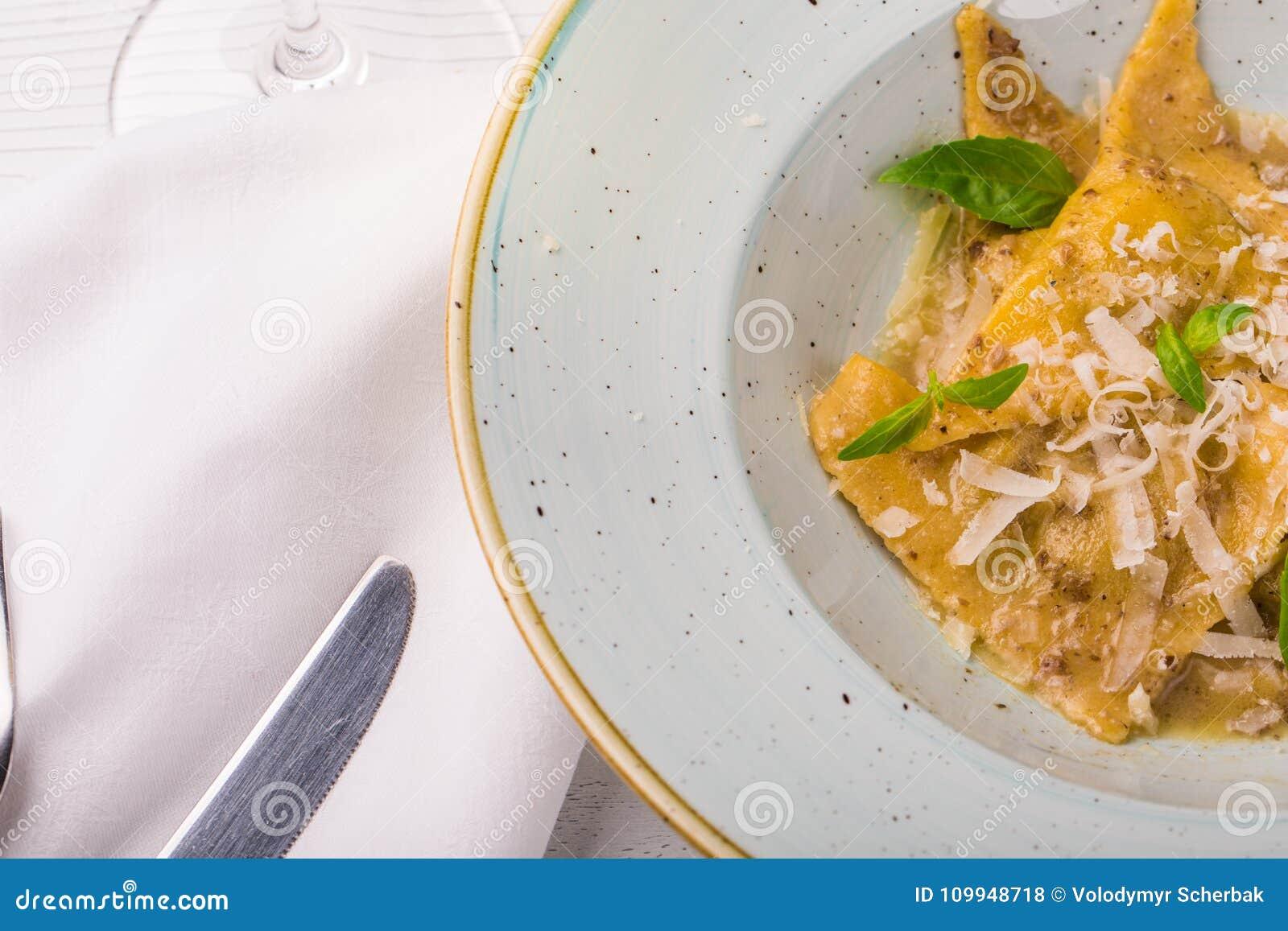 Italiensk raviolitortellini med basilika- och parmesanost på en vit platta