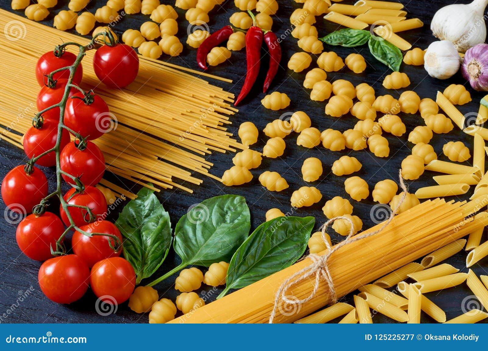 Italiensk traditionell mat, kryddor och ingredienser för att laga mat som basilika, körsbärsröda tomater, chilipeppar, vitlök och