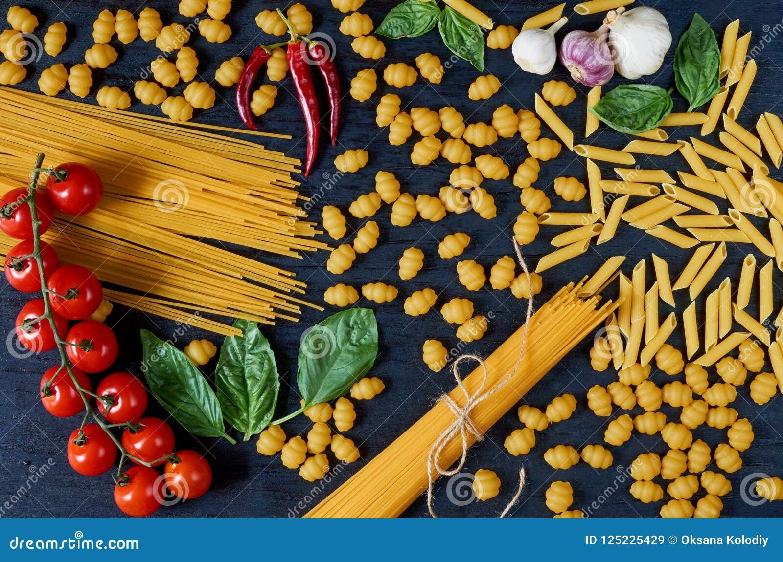 Italiensk traditionell mat, kryddor och ingredienser för att laga mat som basilikasidor, körsbärsröda tomater, chilipeppar, vitlö
