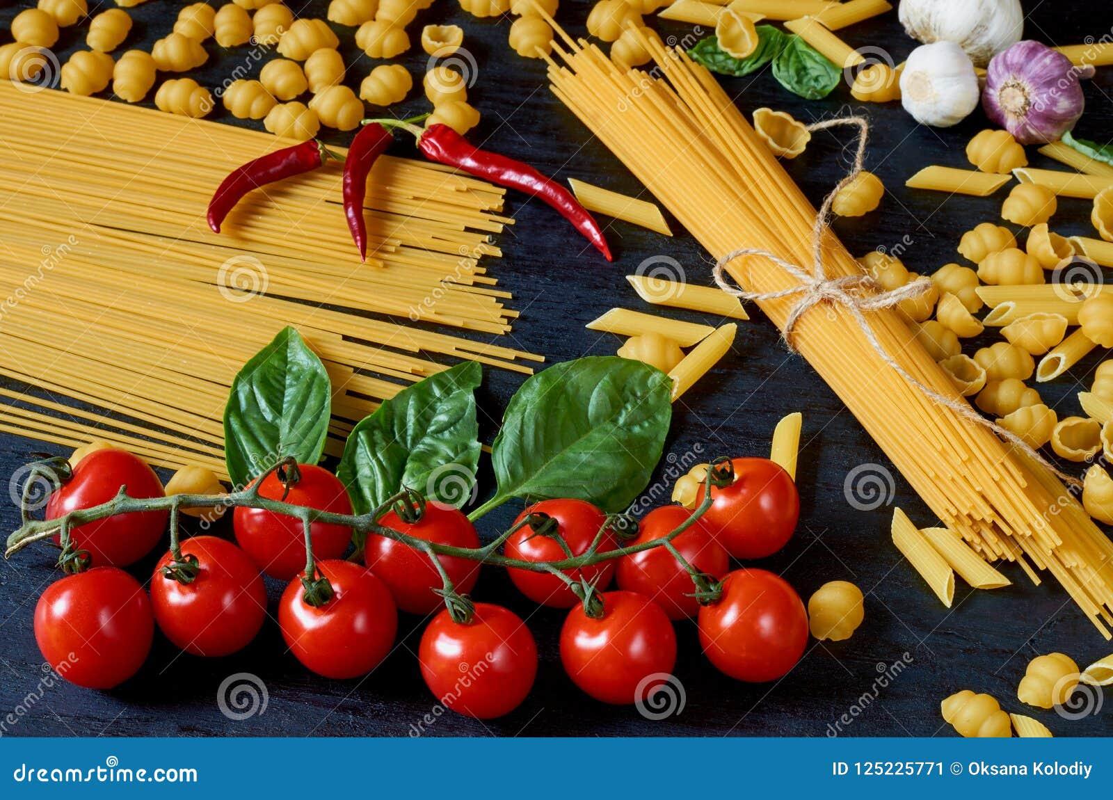 Italiensk traditionell mat, kryddor och ingredienser för att laga mat som körsbärsröda tomater, chilipeppar, vitlök, basilikasido