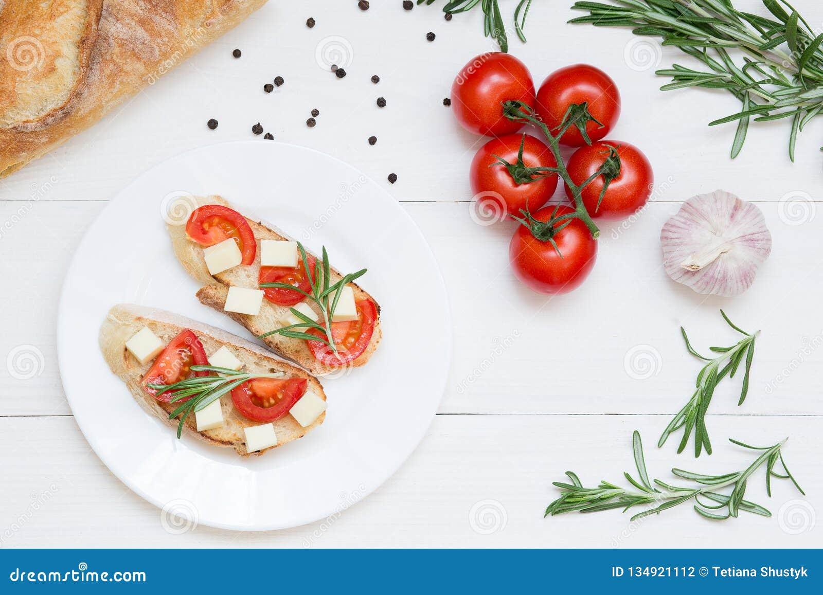Italienska bruschettarostade bröd med tomater och ost på vit träbakgrund, bästa sikt