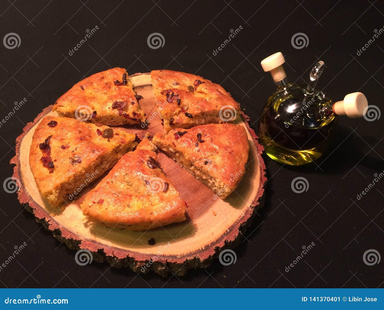 Italienskt focacciabröd på ett träbräde med balsamic vinäger och extra jungfrulig olivolja