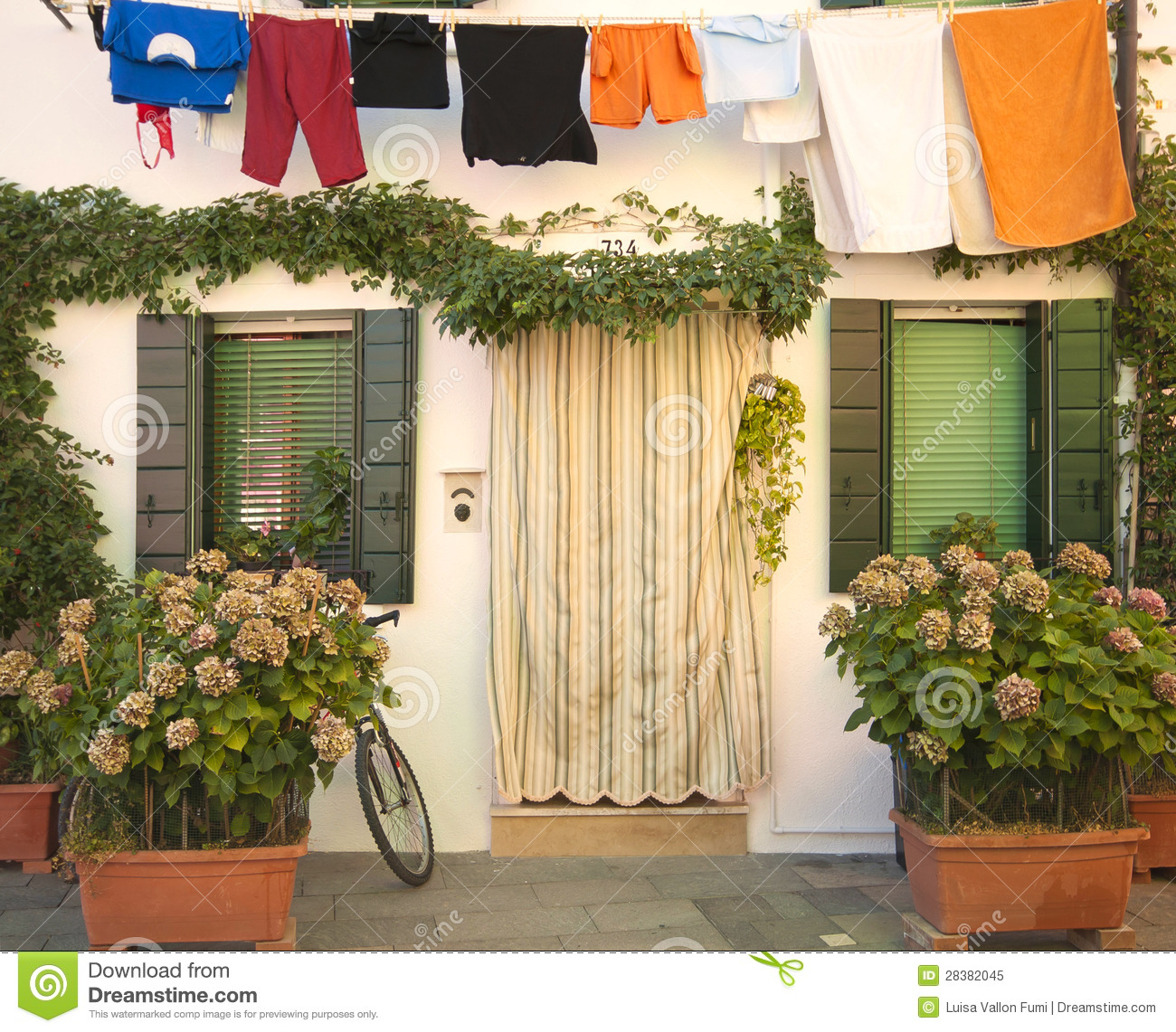 italy, burano: house with flowers and laundry hanging royalty free