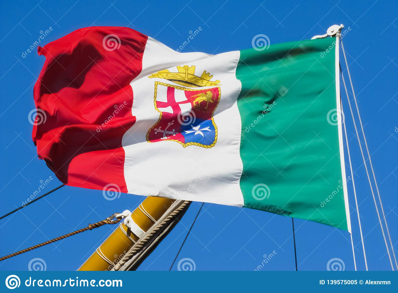 The naval flag of Italy flutters on the mast.