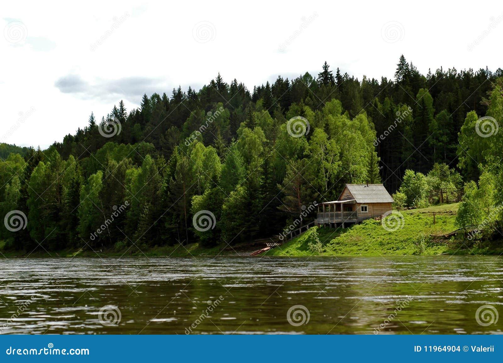Izba en el taiga y el río siberianos Mana de la montaña