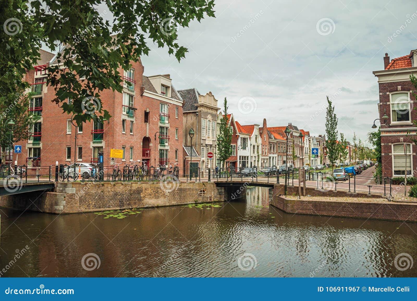 Izolujący kanał z mostem, drzewami i ceglanymi domami w chmurnym dniu przy Gouda bascule,