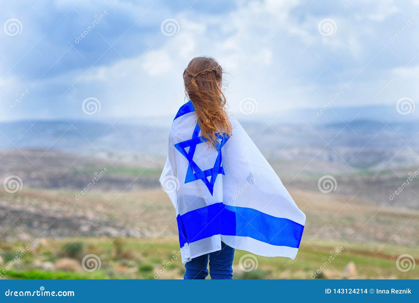 Izraelicka żydowska mała dziewczynka z Izrael flagą z powrotem przegląda
