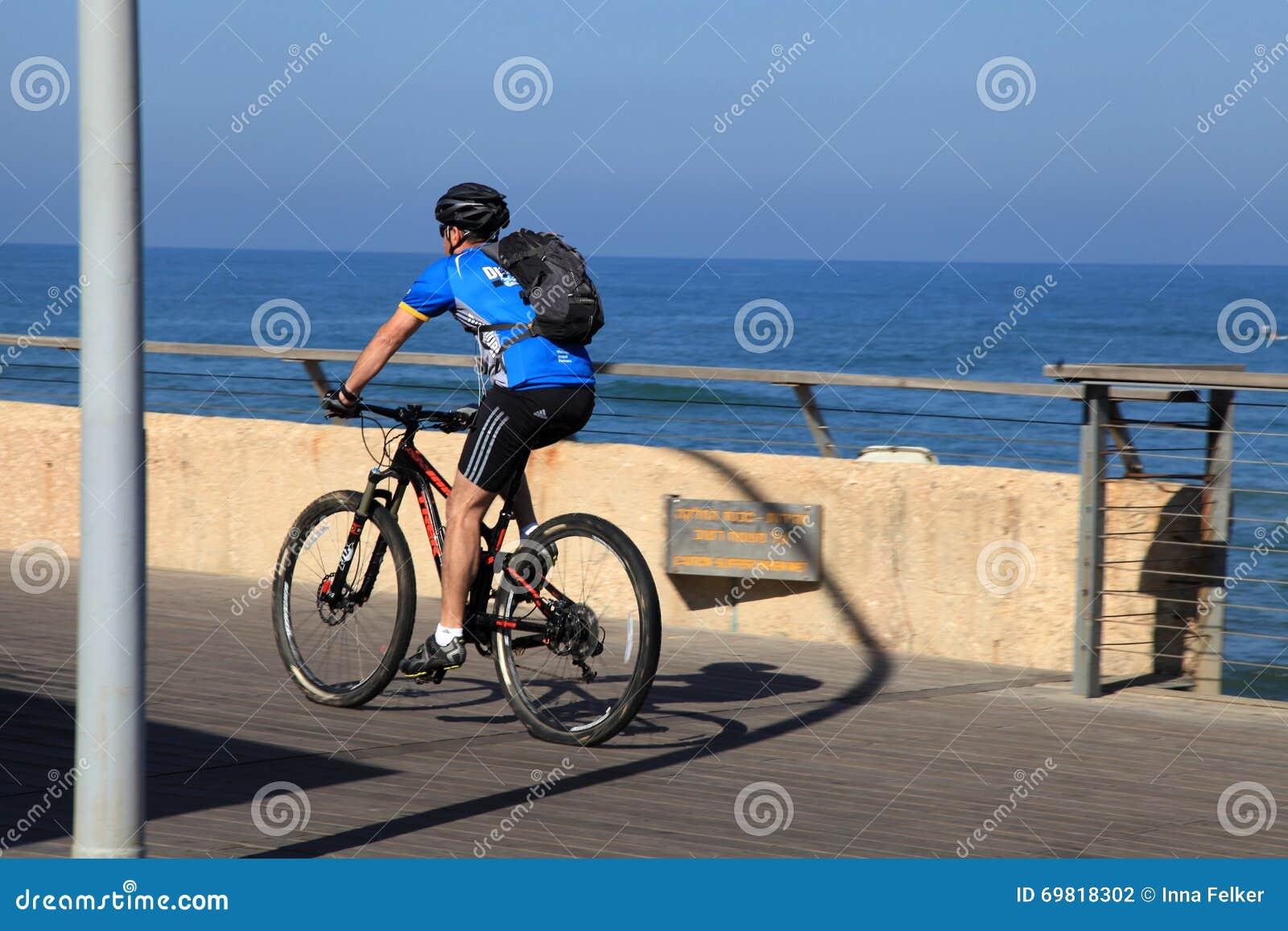Izraelicki mężczyzna przejażdżki rower na dennym deptaku w Tel Aviv, Izrael