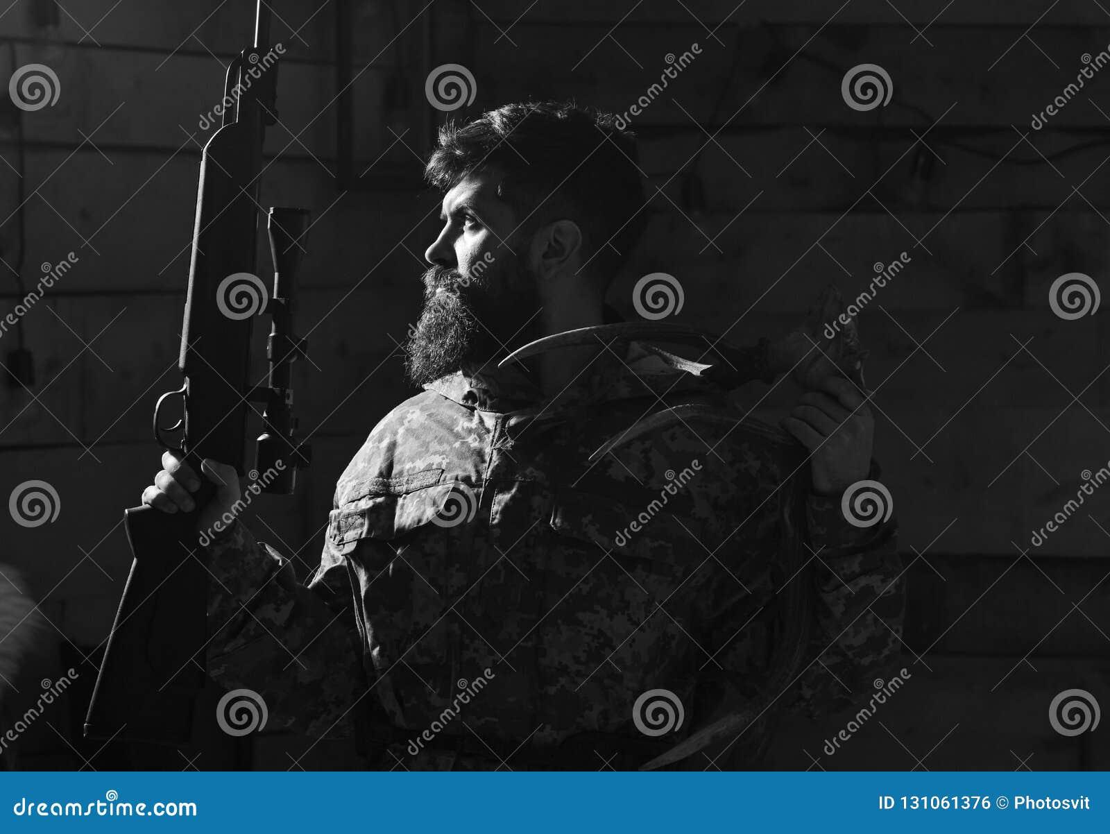 Jägarebegrepp Ståenden av den skäggiga moderna jägaren med hans troféhåll plundrar Mannen med skägget bär kamouflagekläder