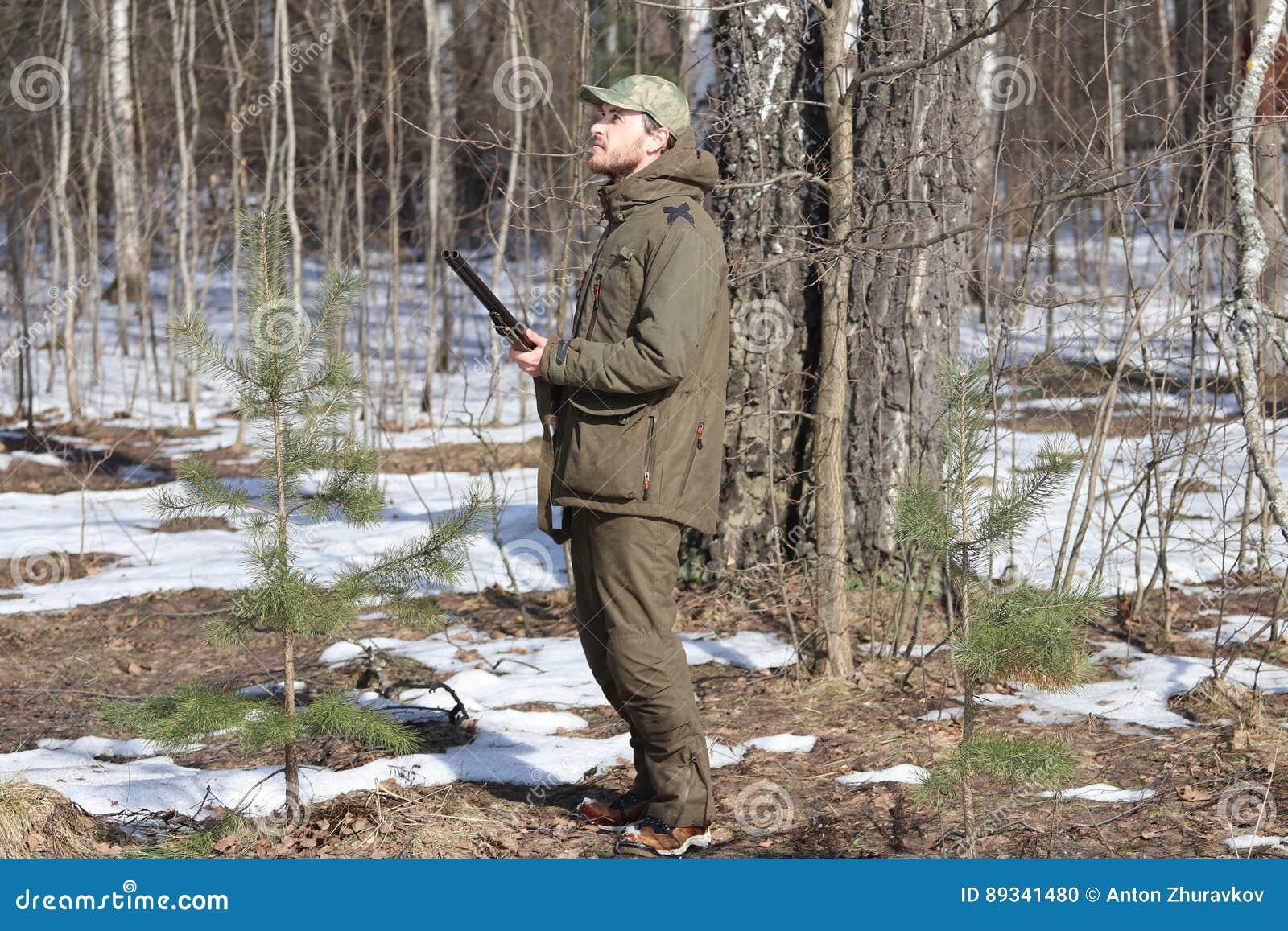 Jägermann in der dunklen kakifarbigen Kleidung im Wald