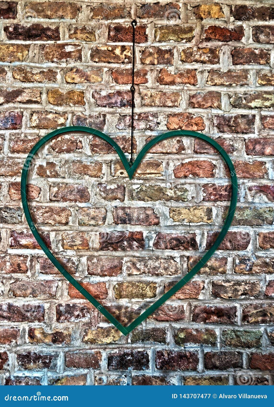 Järnhjärta som hänger på en tegelstenvägg