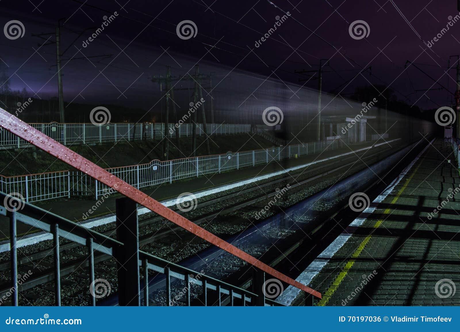Järnvägsstation på natten med ett övergående drev