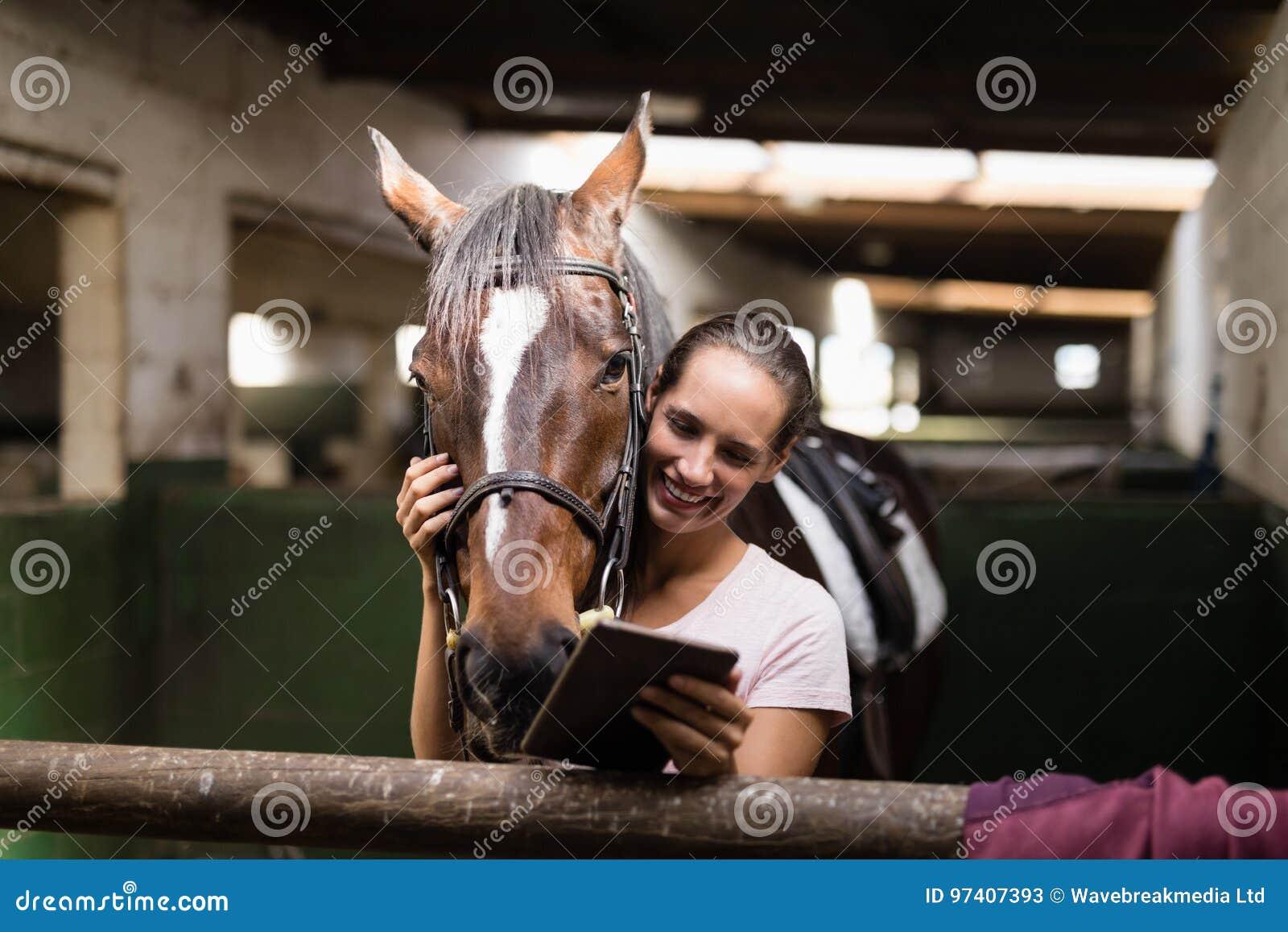 Jóquei fêmea de sorriso que usa a tabuleta digital ao estar pelo cavalo