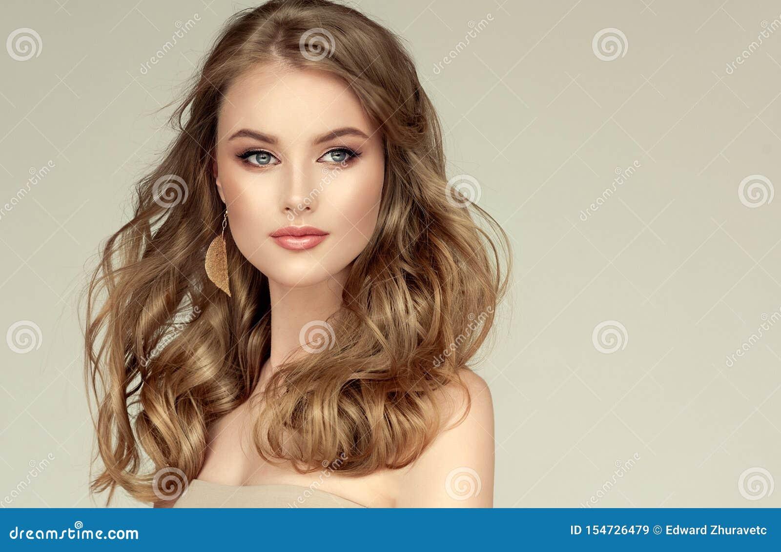 Jóvenes, modelo hermoso cabelludo rubio con el pelo largo, bien preparado, vestido en pendientes de oro Peinado libremente de col
