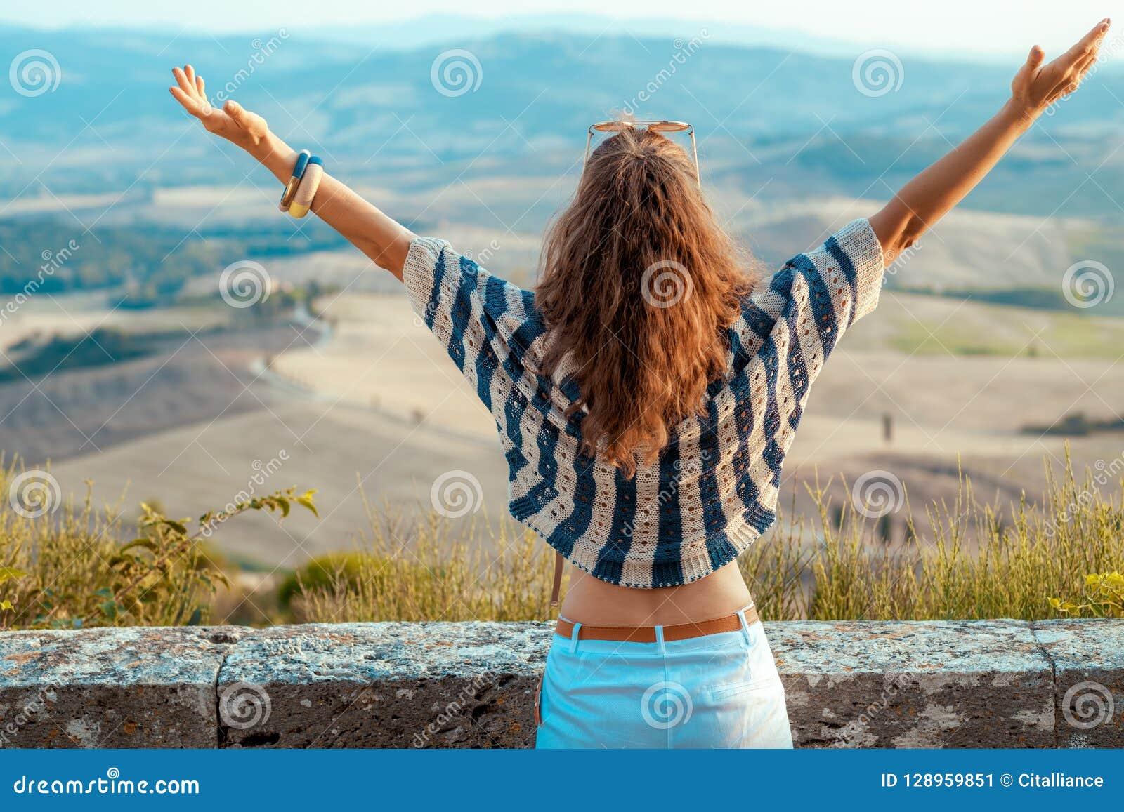 Júbilo moderno de la mujer del viajero contra el paisaje de Toscana