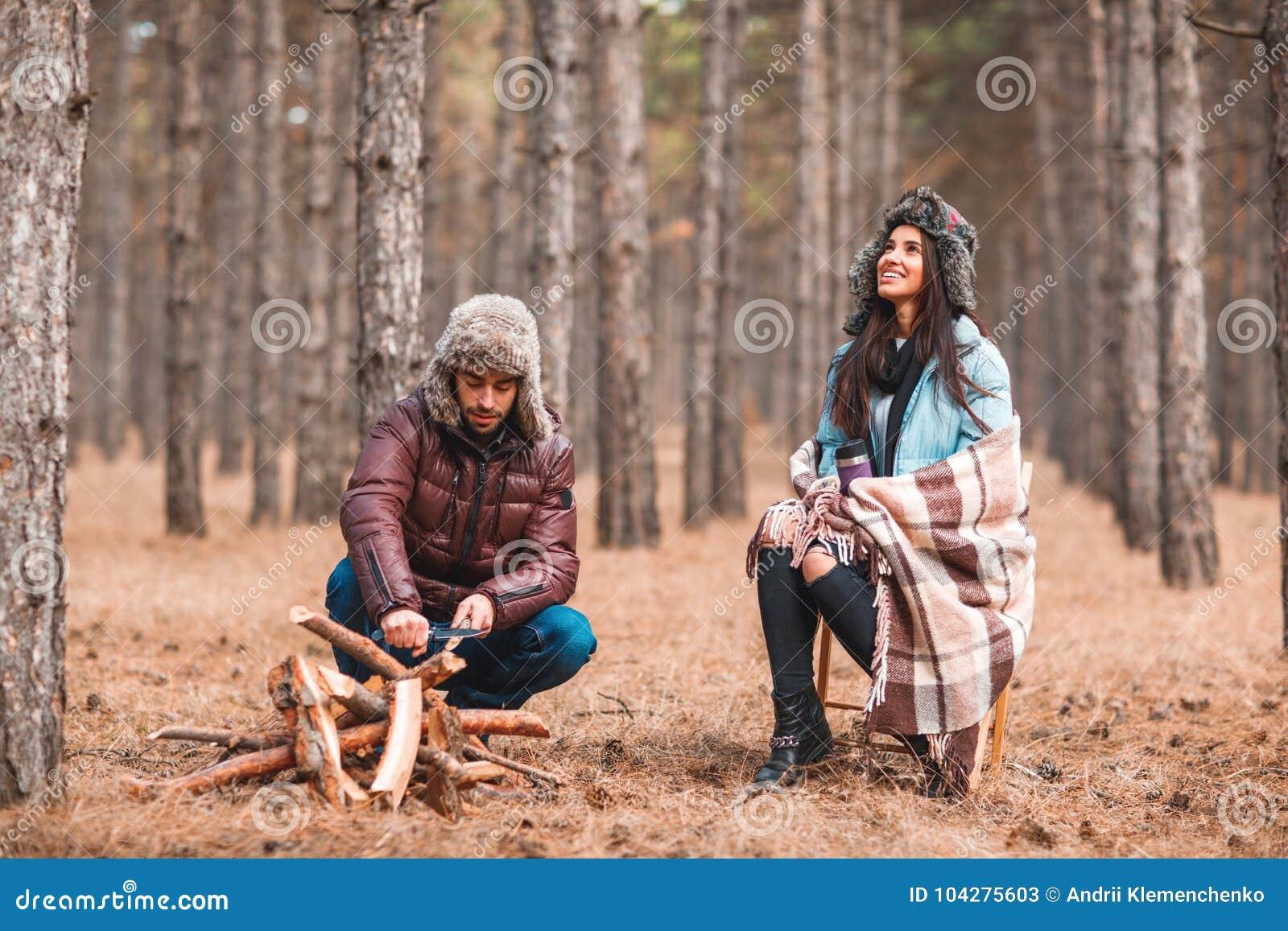 Júntese en la muchacha del bosque A se está sentando cubrió en una manta, el individuo afila los cuchillos de madera