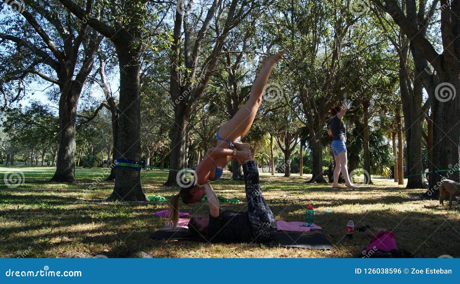 JÚPITER, FLORIDA EUA - 17 DE JUNHO DE 2017 Jovens mulheres que fazem a ioga & o slackline do acro em um parque público em Florida
