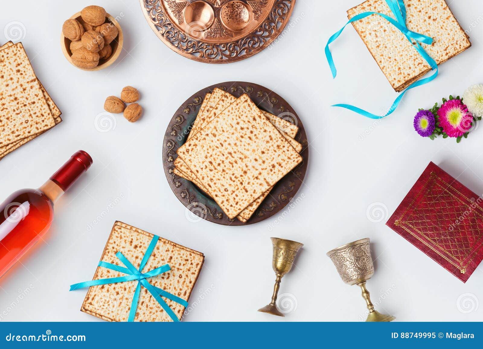Jüdisches Passahfestfeiertag Pesah-Feierkonzept mit Matzoh, Wein und seder Platte über weißem Hintergrund Ansicht von oben flache