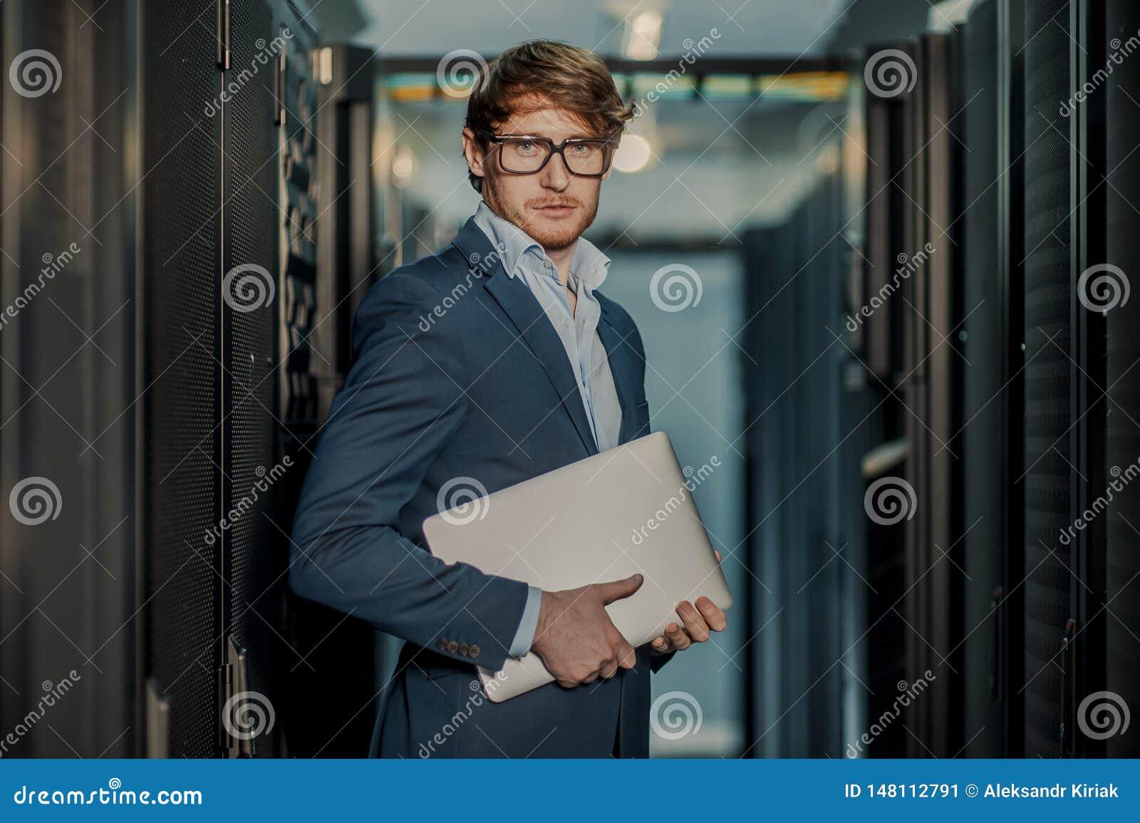 J?venes ?l hombre de negocios del ingeniero con el ordenador port?til de aluminio moderno fino en sitio de servidor de red