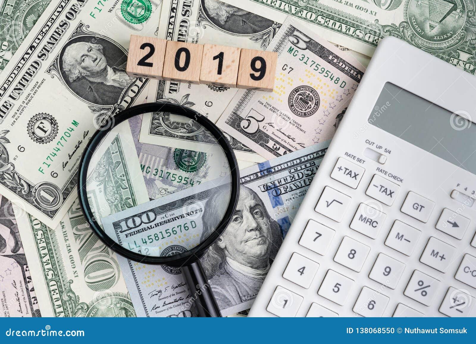 Jaar 2019 die naar financieel succes zoeken of winst of belastingsberekeningsconcept, zwart vergrootglas met houten kubus vinden