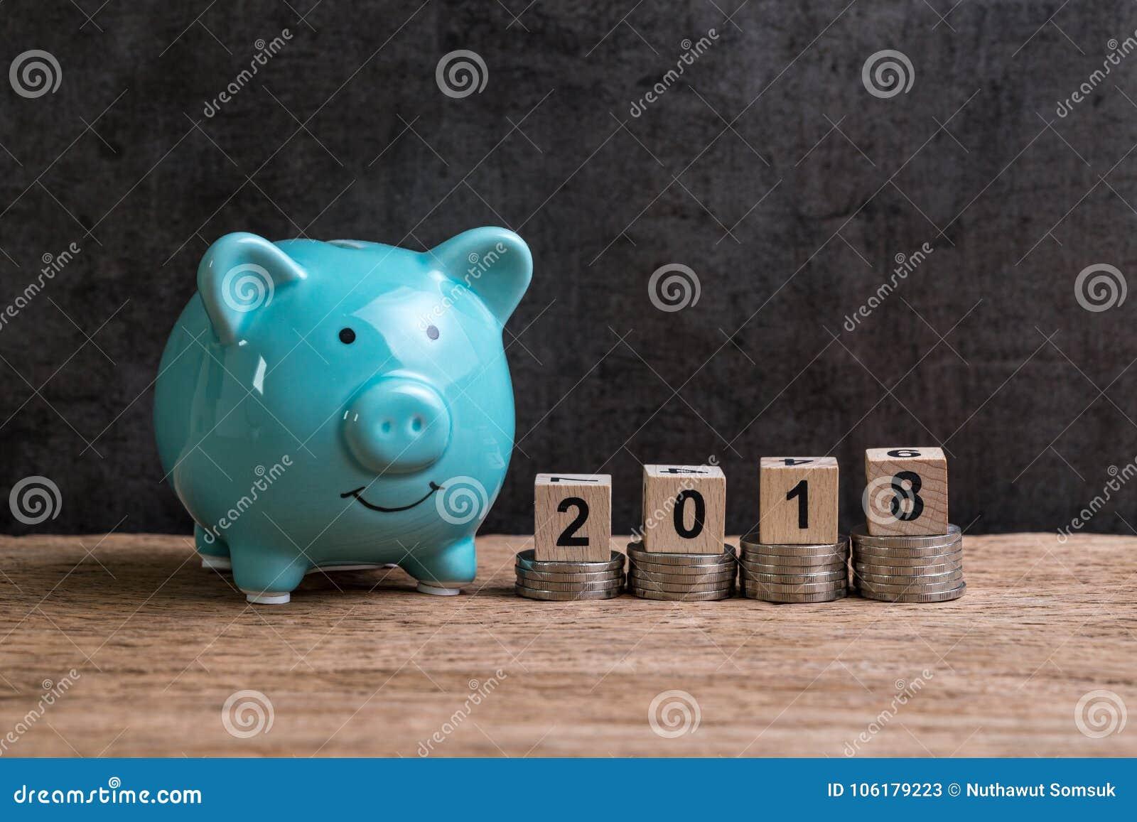 Jaar 2018 financieel doel met spaarvarken en stapel muntstukken en