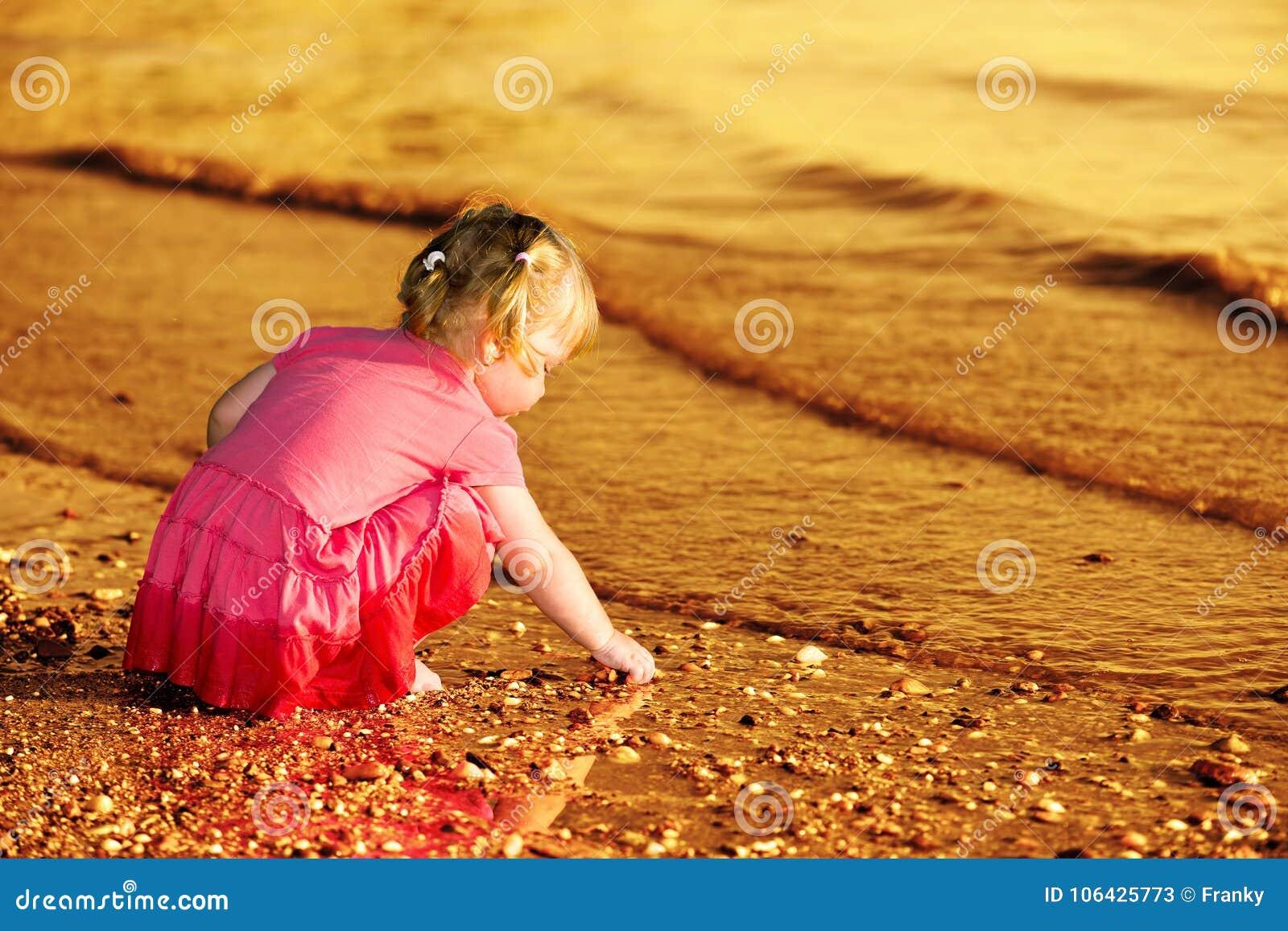 2-3 jaar het oude meisje spelen met kiezelstenen bij riverbank
