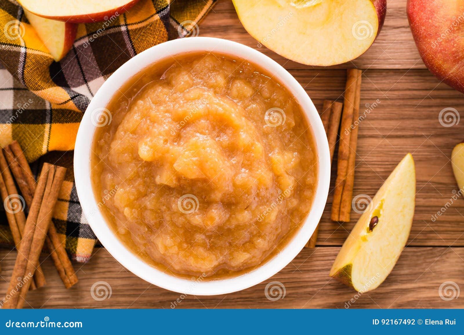 Jabłczany puree, jabłka i cynamon na drewnianym stole,