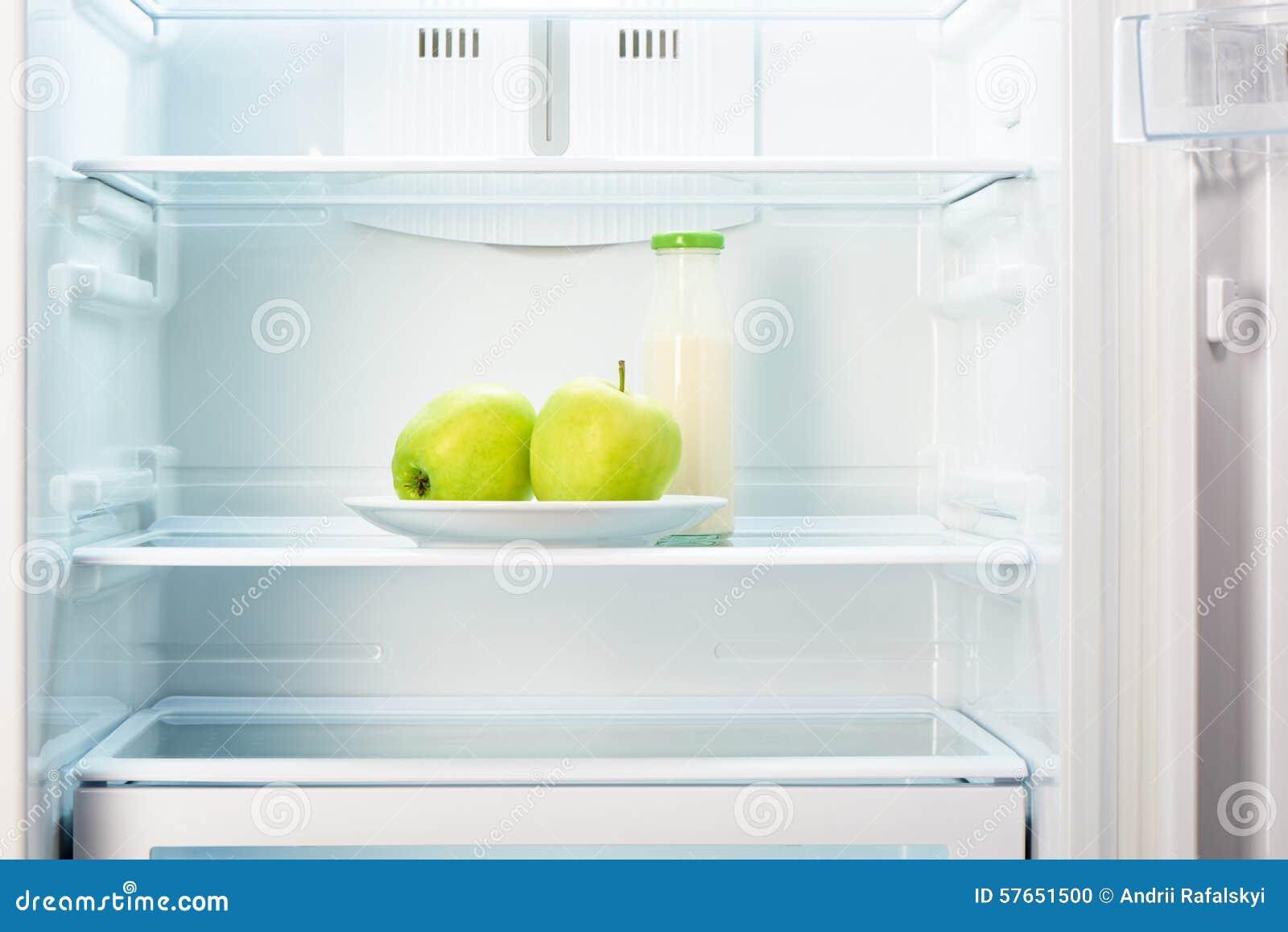 Jabłka na bielu talerzu z butelką jogurt w chłodziarce