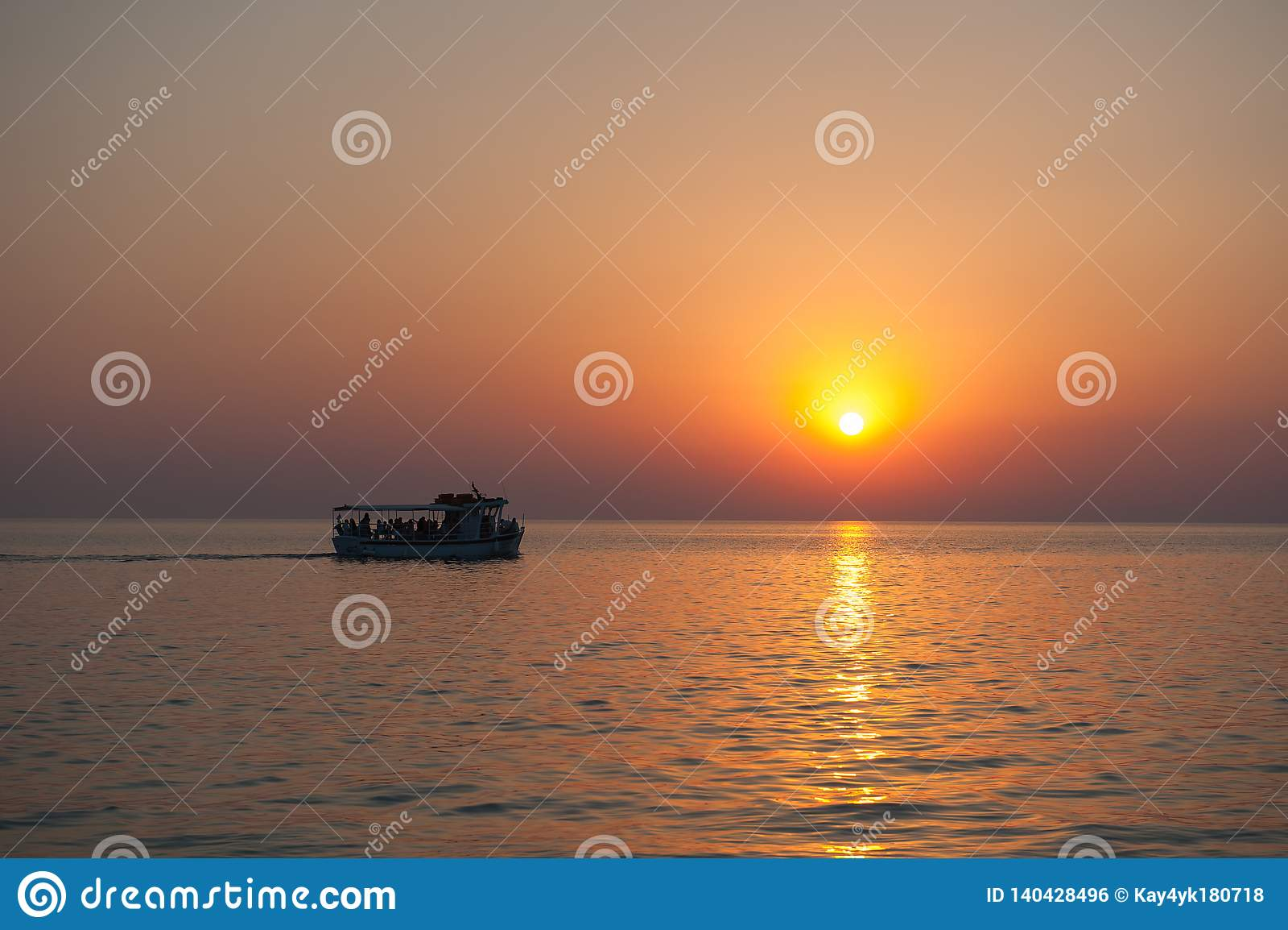 Jacht met toeristen bij zonsondergang met vogels die wegvliegen