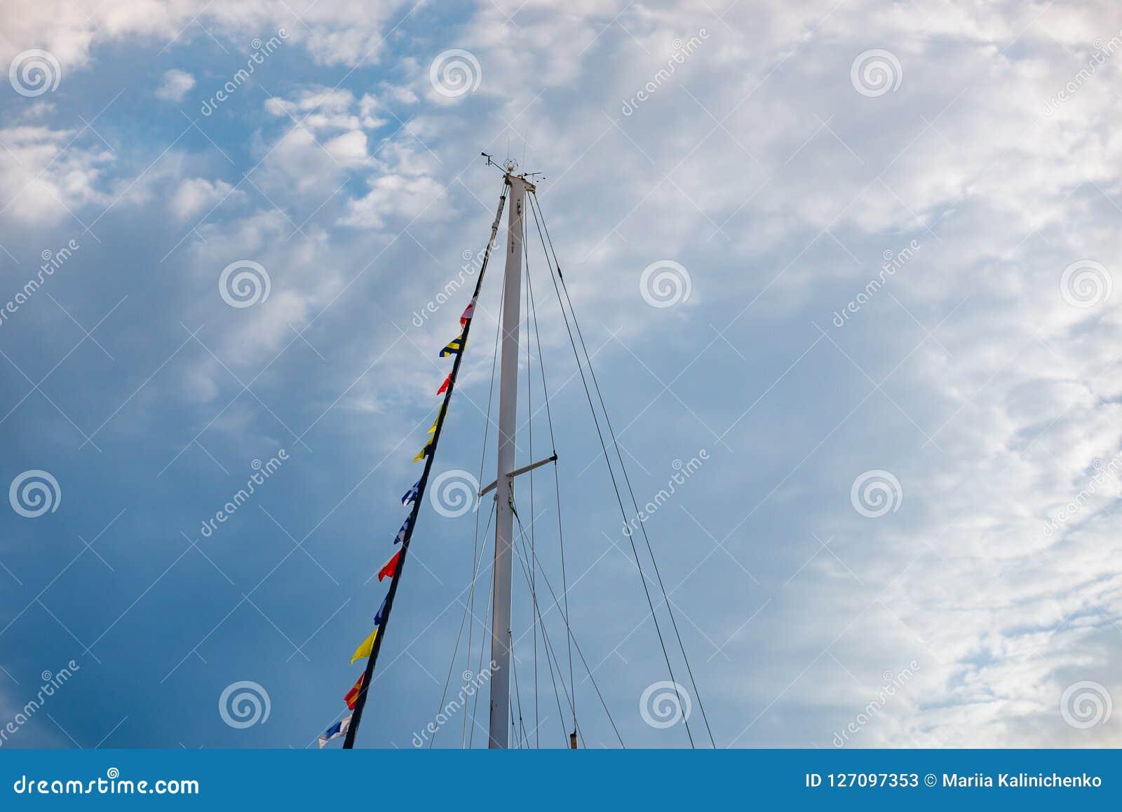 Jachtmasten met feestelijke vlaggen tegen blauwe hemel met wolken