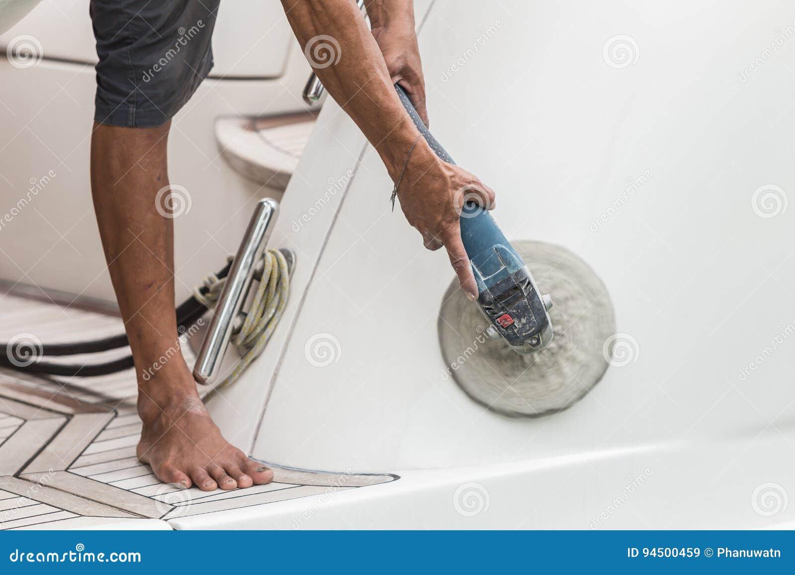 Jachtonderhoud Een mens het oppoetsen kant van de witte boot in