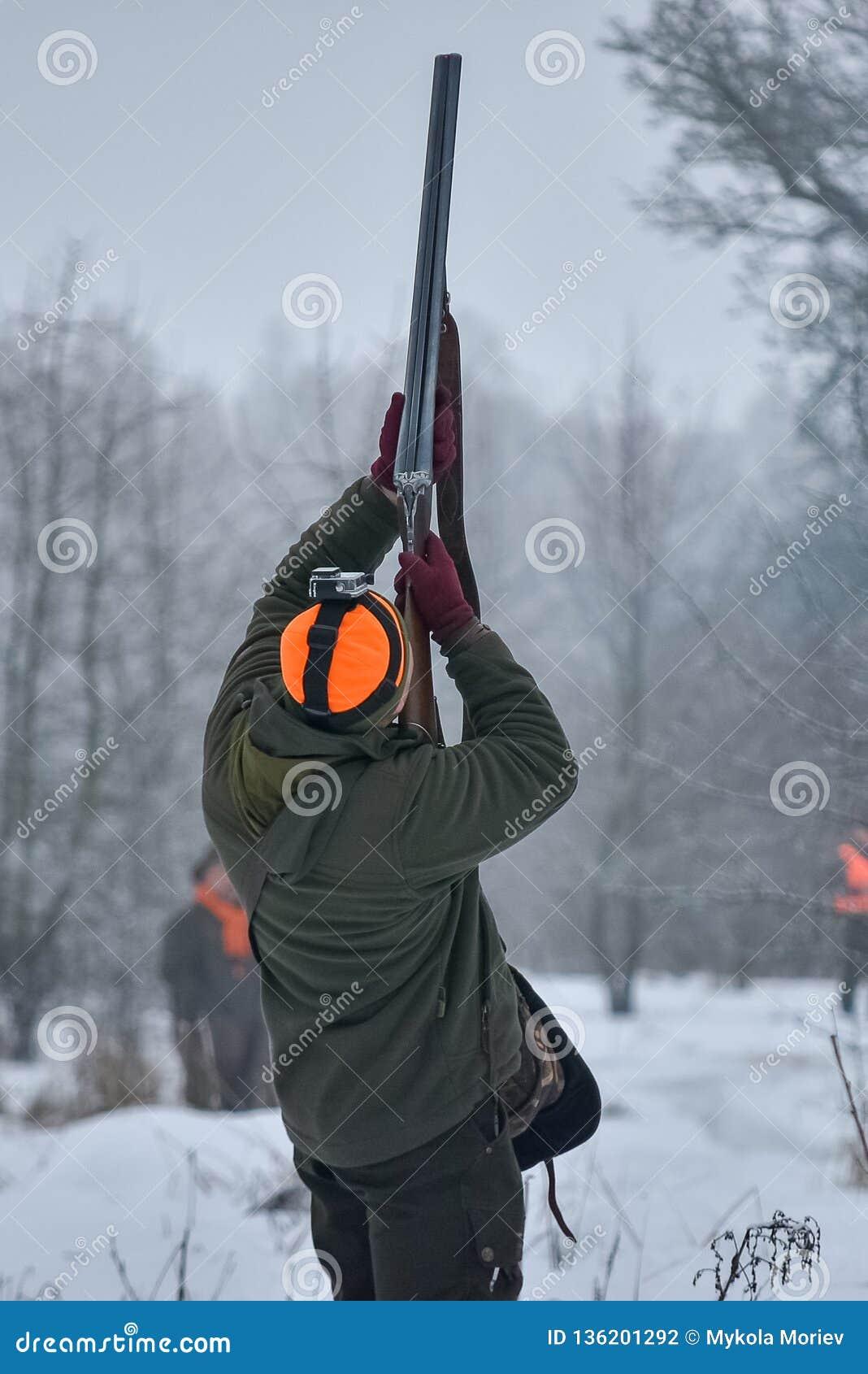 Jachtseizoen, vogel de jacht De jager schiet op de vogels die boven hem vliegen