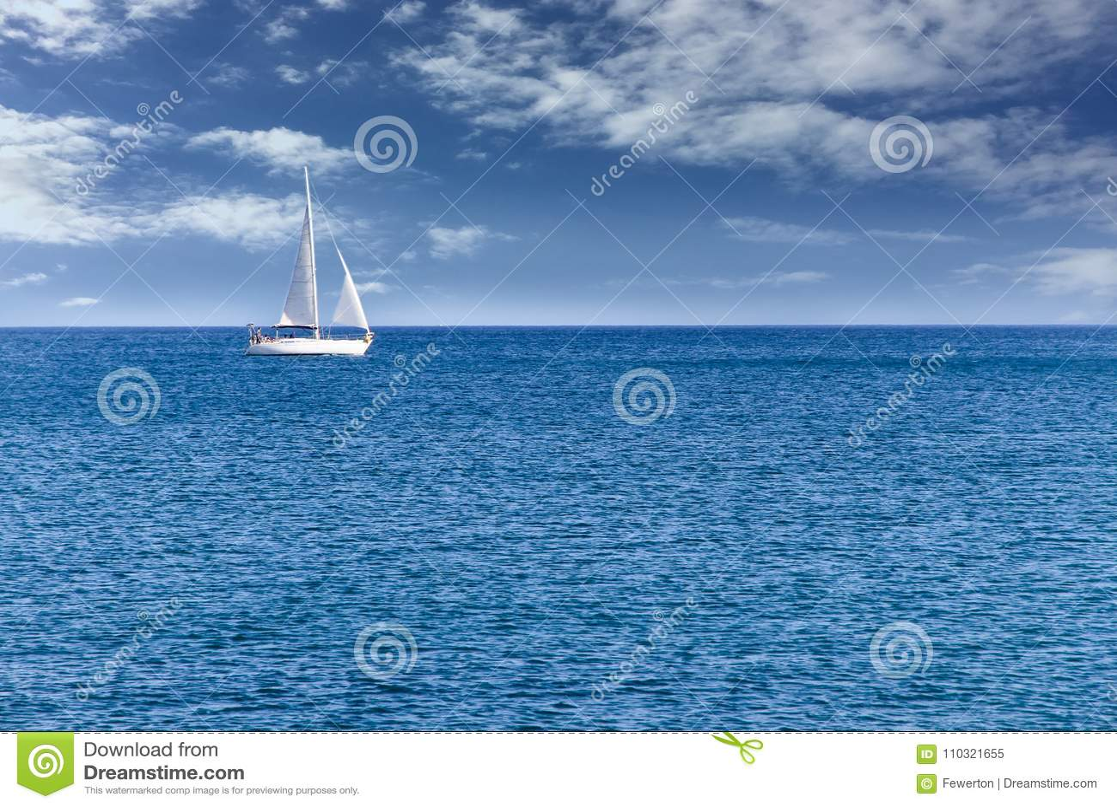 Jachtzeilboot die alleen op kalme blauwe zeewaters op een mooie zonnige dag met blauwe hemel en witte wolken varen